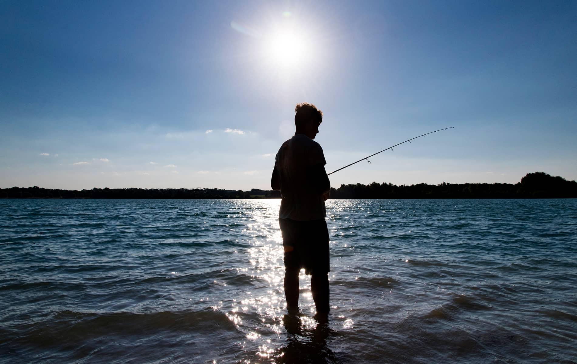 Pêcheur au leurre à contre jour