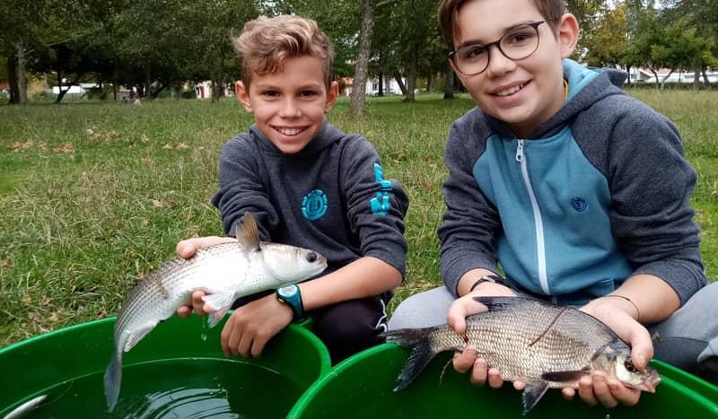 Deux jeunes pêcheurs avec leurs prises respectives